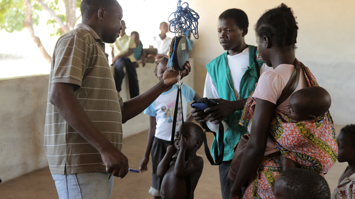 Community health worker in Zambezia helps weigh children and teach families about proper nutrition for children.